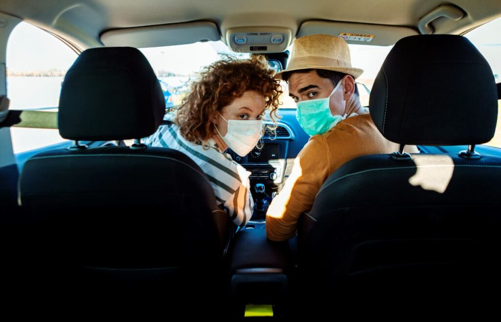 couple in masks driving in car