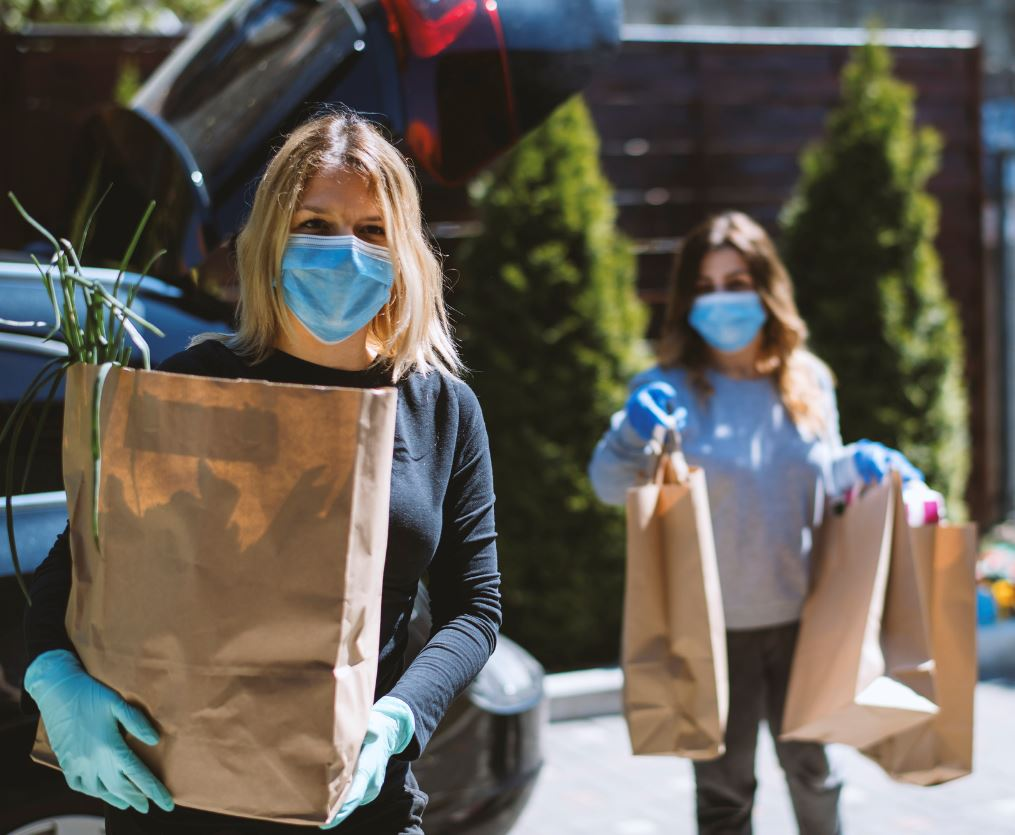 Women wearing gloves carrying groceries to car