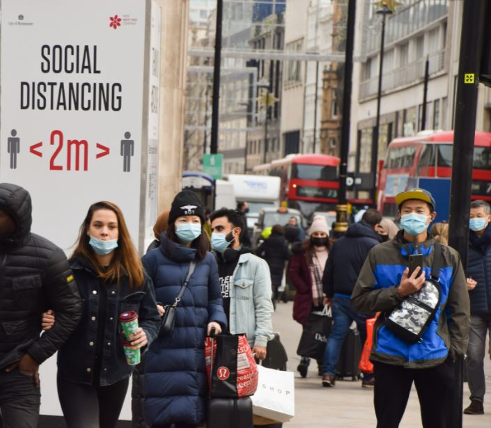 people walking wearing masks in london
