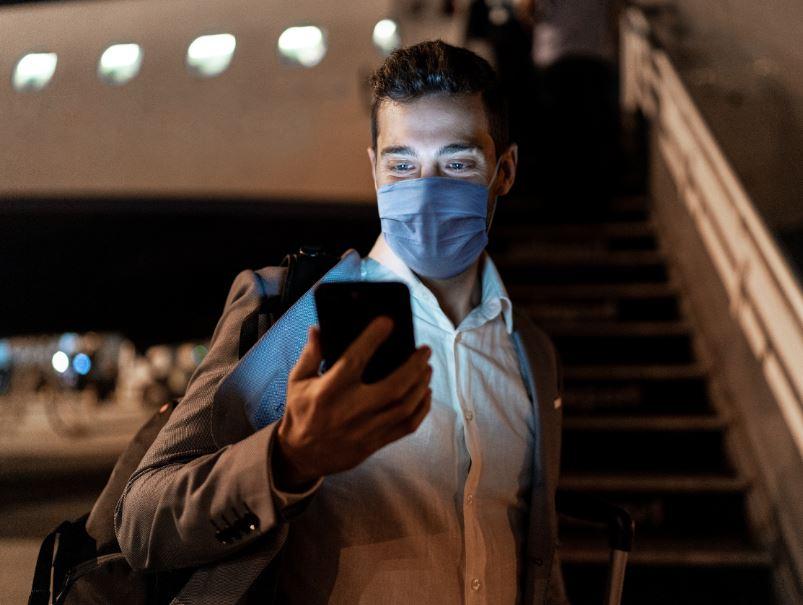 man-mask-plane-phone