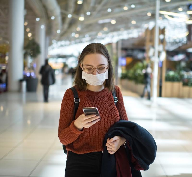 mask traveler smartphone airport