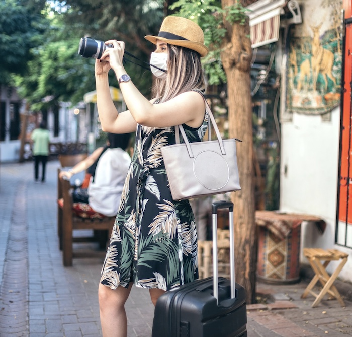 tourist wearing protective face mask taking photos