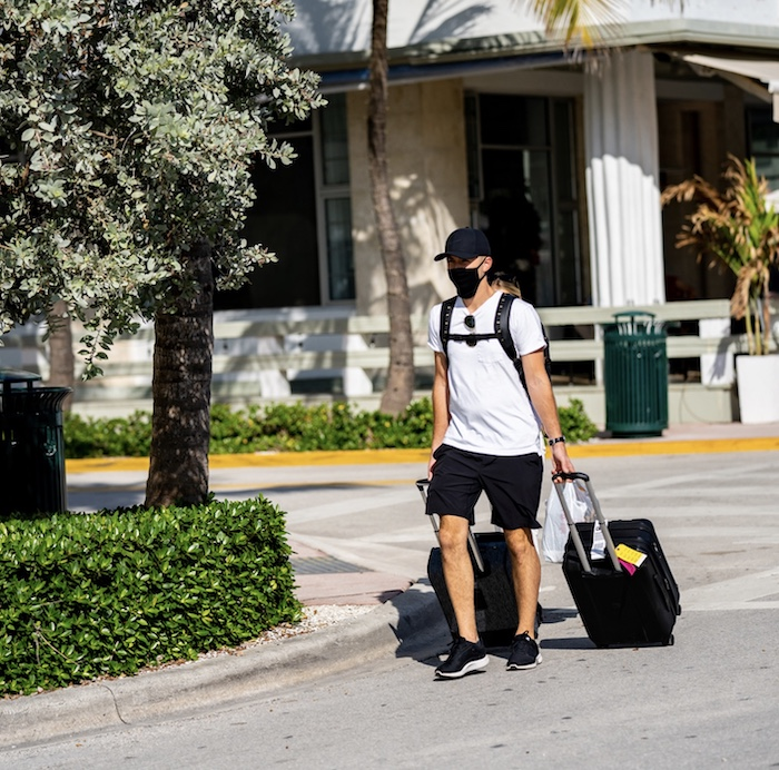 tourists walking in Miami Beach with luggage suit cases