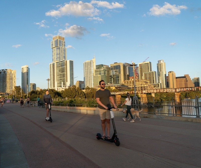 Riding Scooters over the Colorado River or Town Lake using the Pedestrian Bridge in Downtown Austin Texas at Sunset