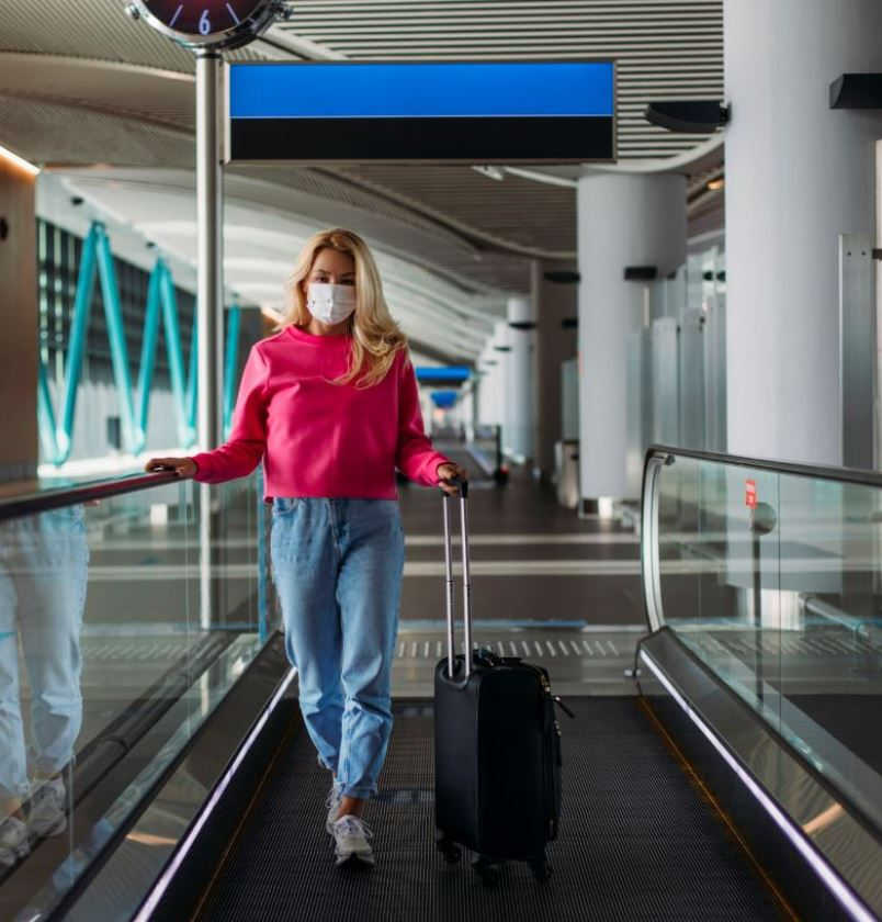 Woman Arriving At Airport Wearing Mask