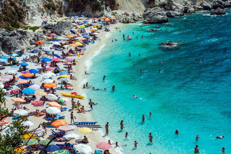 beach in greece packed with tourists