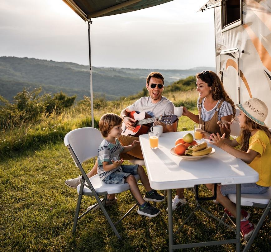 family eating smiling by camper van