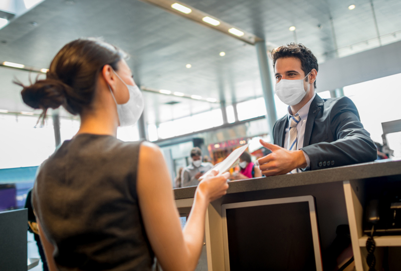 man doing the check-in at the airport wearing a facemask