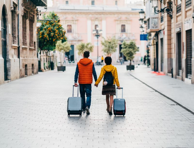 spain couple travlers suitcases street