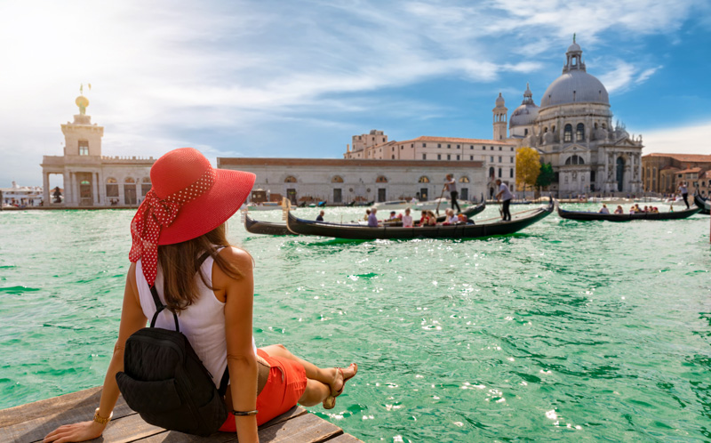 female tourist at Basilica di Santa Maria della Salute and Canale Grande in Venice, Italy