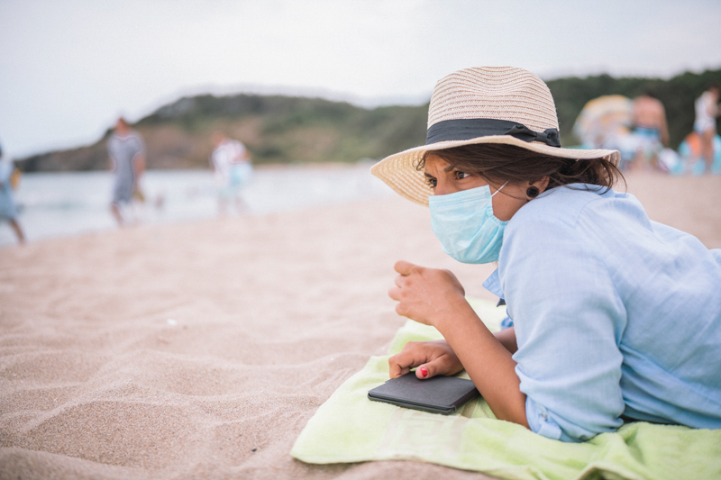 woman with protective face mask on the beach