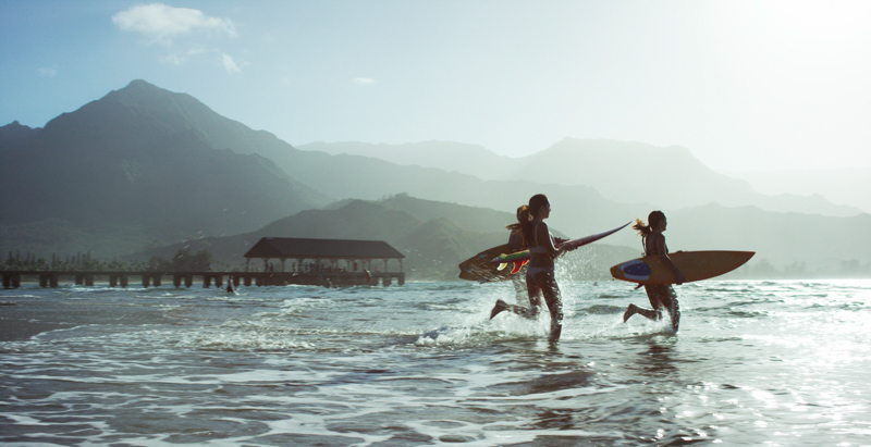 Three people on a beach, running into the ocean with surfboards