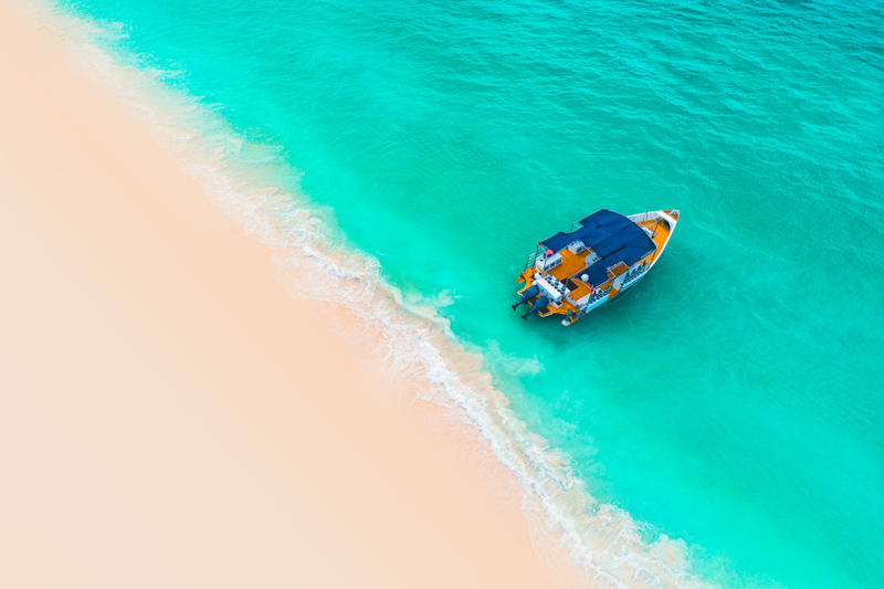 Beautiful caribbean sea and boat, aerial view from the beach.