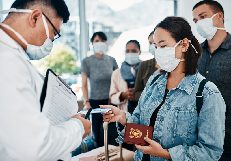 woman wearing a mask and giving her docs to a doctor in an airport