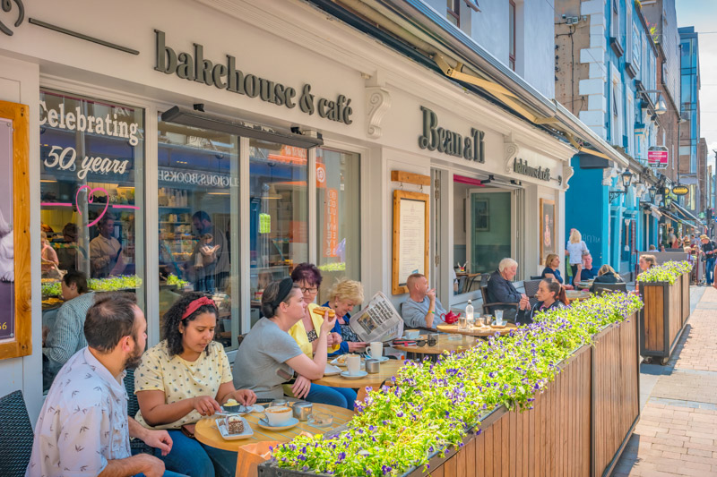 People enjoy a sunny day on the patio of a cafe in downtown Limerick, Ireland.