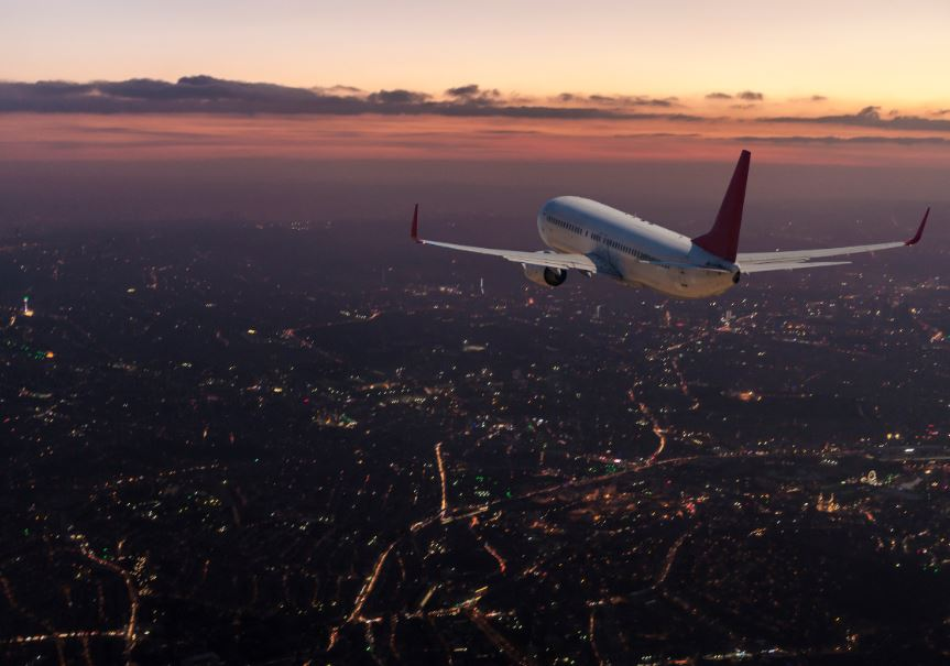 airplane flying city dusk