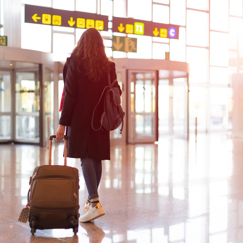 Rear view of brunette woman exit from airport with trolley (hand luggage)