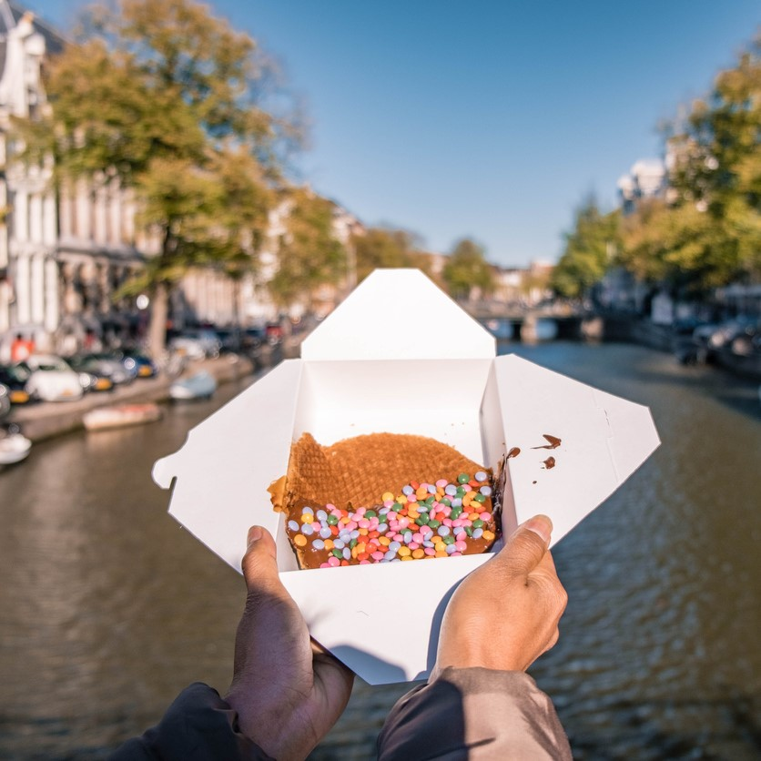 woman hand with Stroopwafel in Amsterdam - typical Dutch food - two circular pieces of waffle filled with caramel-like syrup