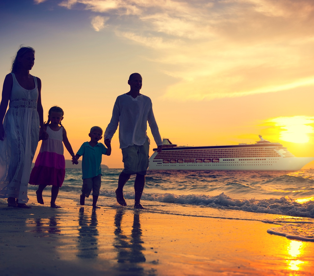 family of four holding hands walking on the beach while on a cruise. sunset and cruise ship in the background.