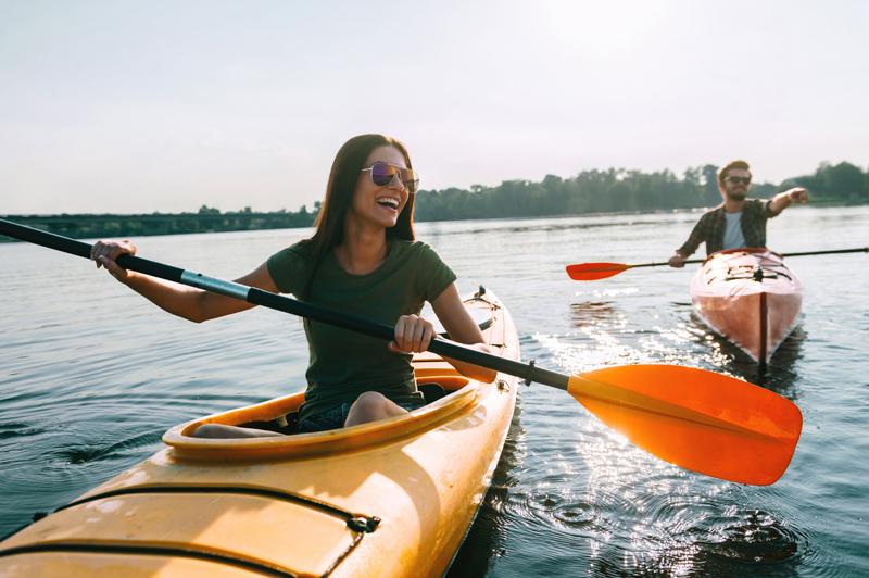 couple kayaking on lake together and smiling