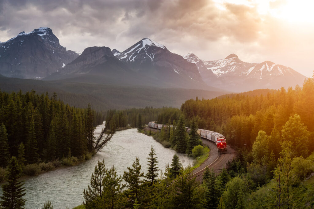 Iconic View of Morant's Curve with Train Passing and Canadian Rocky Mountain Landscape in the background during colorful sunset. Located in Banff National Park, Alberta, Canada.