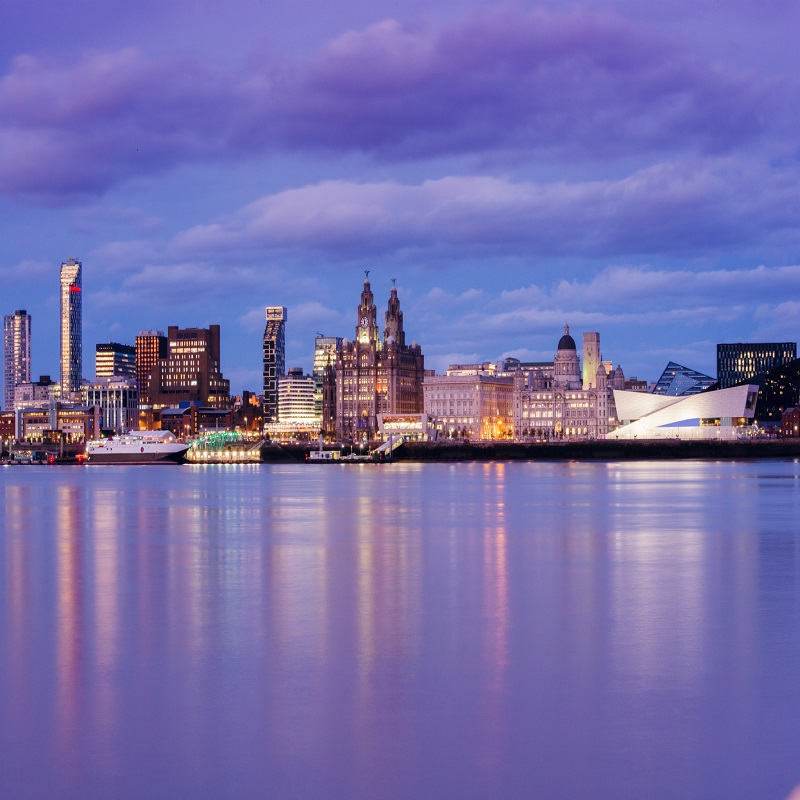 This is a horizontal, color photograph of Liverpool England at dusk. The docks are visible along the city skyline across the River Mersey