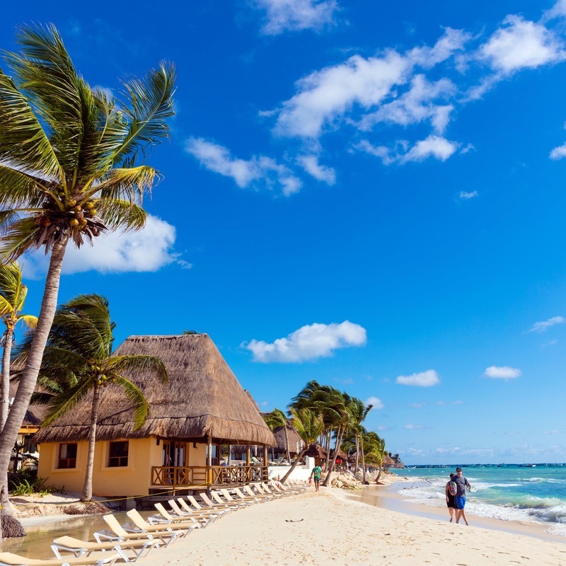 Playa del Carmen, Mexico - Unidentified people walking in white sand on the north beach of Playa del Carmen in Mexico.