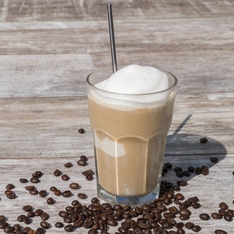 glass of iced veracruz coffee with coffee beans sprinkled around it and a metal straw in the glass