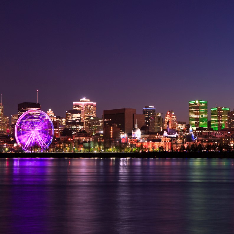 Montreal skyline at night reflected on Saint Lawrence River in Quebec, Canada