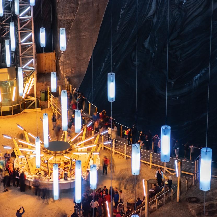 Hall of Salt Mine Salina Turda museum. popular travel destination. people looking in to the pit