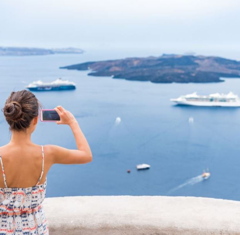 woman taking a picture of cruise ships sailing in the distance