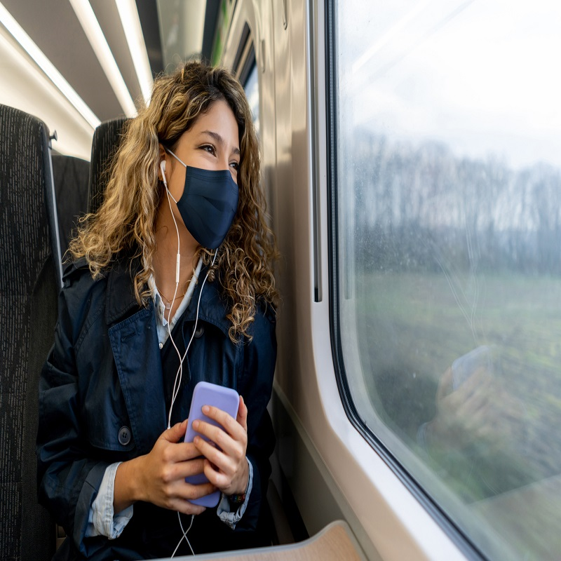 Happy woman traveling by train wearing a facemask