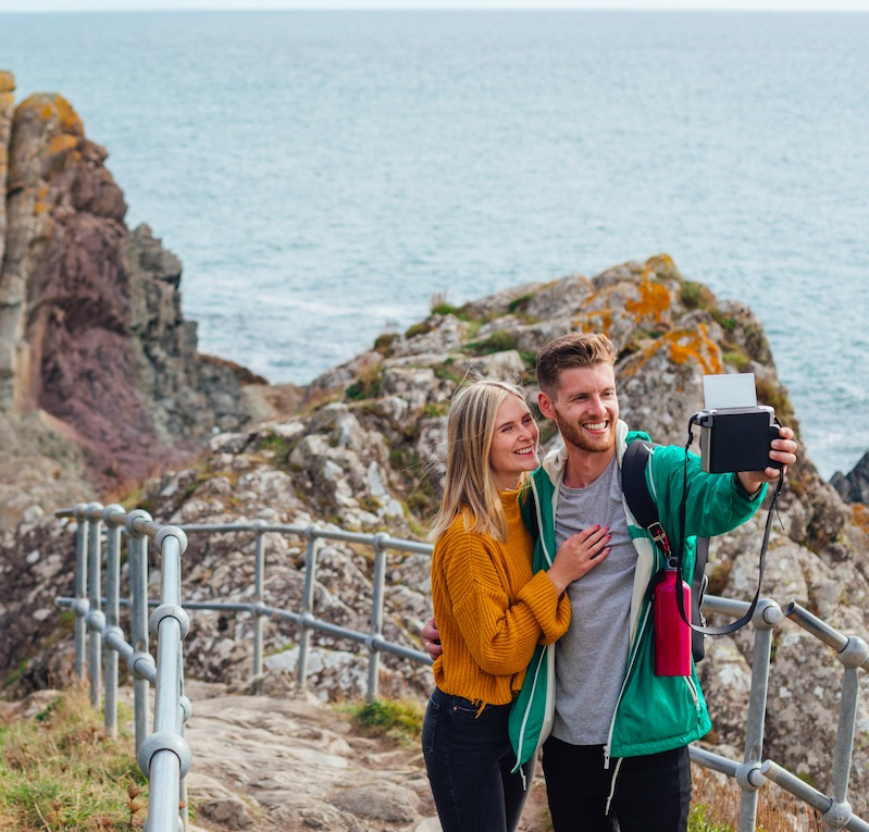 A young caucasian couple are standing by the sea in Polperro, Cornwall, taking a polaroid selfie on their instant camera. They look happy and carefree on their staycation during Autumn.