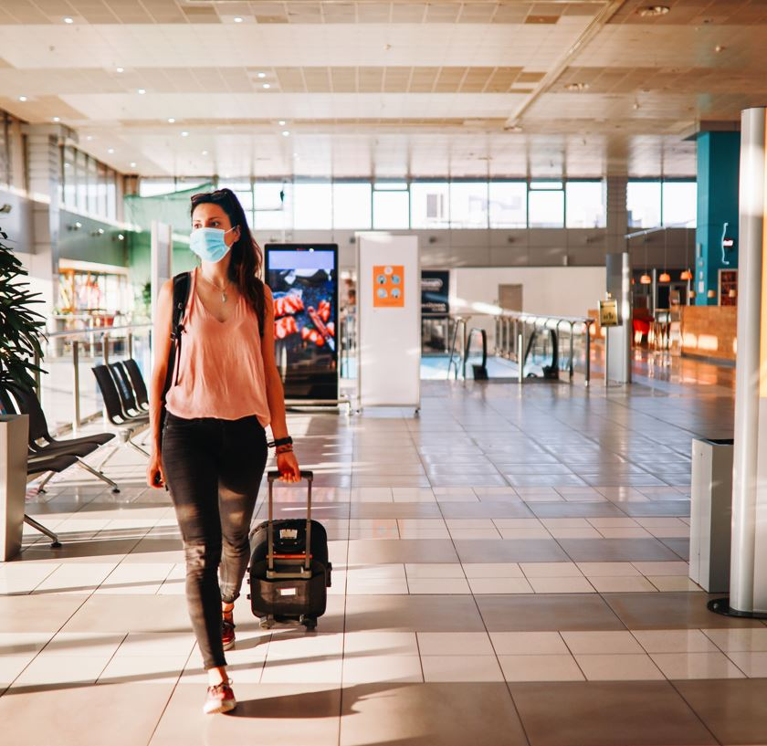 Traveler Wearing Mask with suitcase