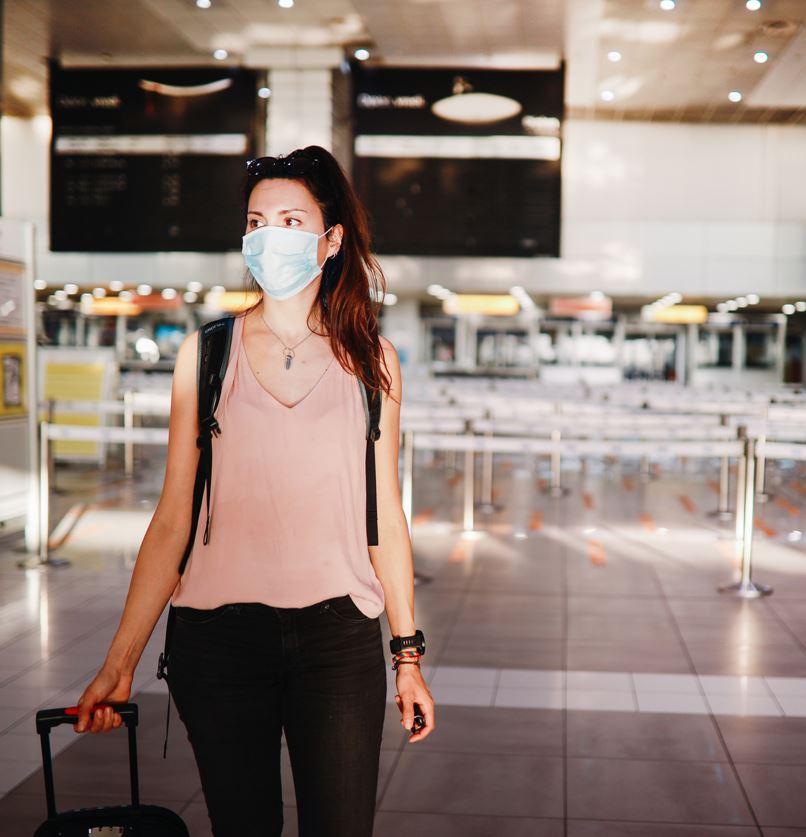 Путешественник в аэропорту Далласа в маске