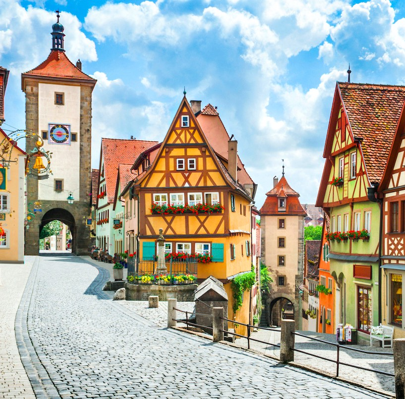 Beautiful postcard view of the famous historic town of Rothenburg ob der Tauber on a sunny day with blue sky and clouds in summer, Franconia, Bavaria, Germany.