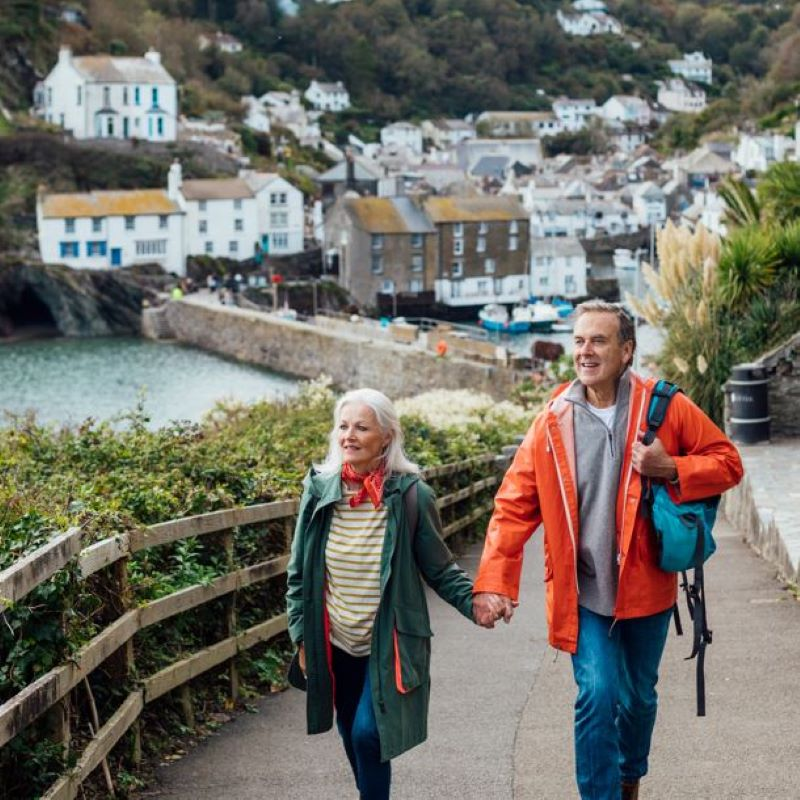 britain uk beach village two people holding hands wearing coats