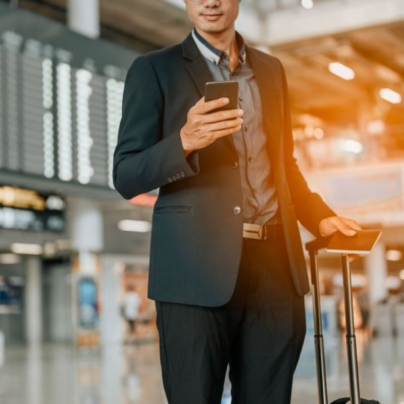 businessman smart phone airport board luggage check in