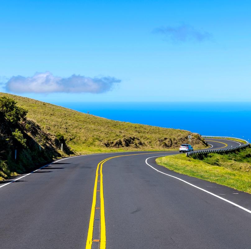 A bright sunny day view of winding Haleakala Highway, against blue sky and blue Pacific Ocean. Haleakala National Park, Maui, Hawaii, USA.