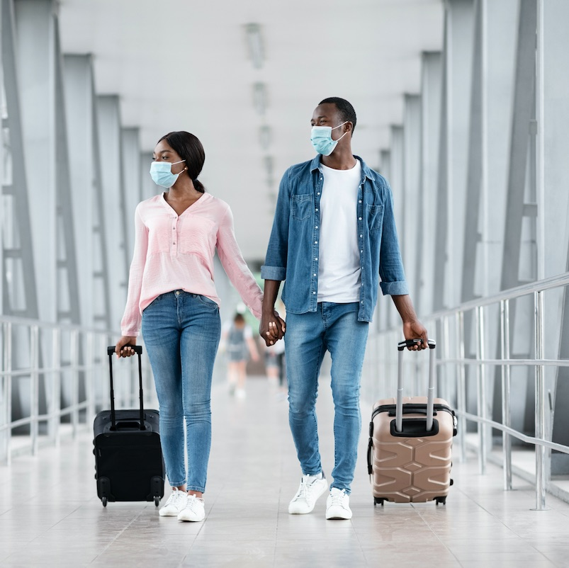 couple walking hand in hand at airport wearing masks