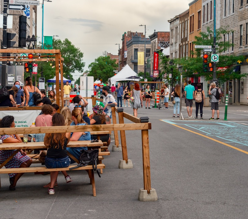 people sitting on patios and walking on a pedestrian street in the summer in downtown Montreal 30 July 2020. Safe active transportation circuit on Mont Royal Avenue during Covid-19 pandemic.