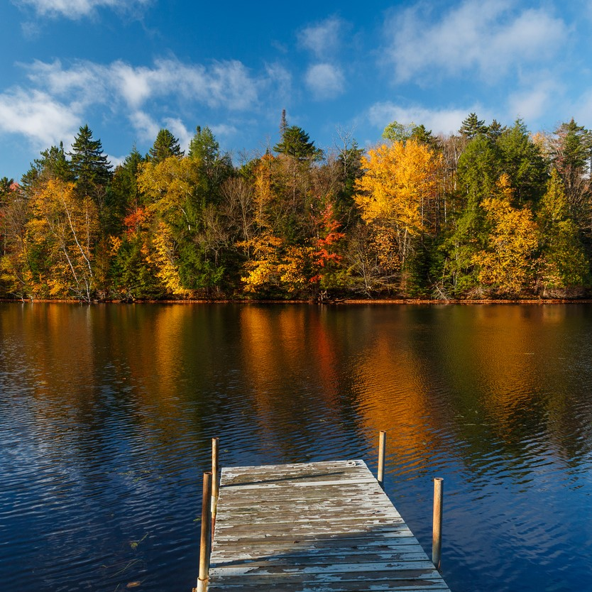 Worn dock on Chateaugay lake, upstate New York in Autumn