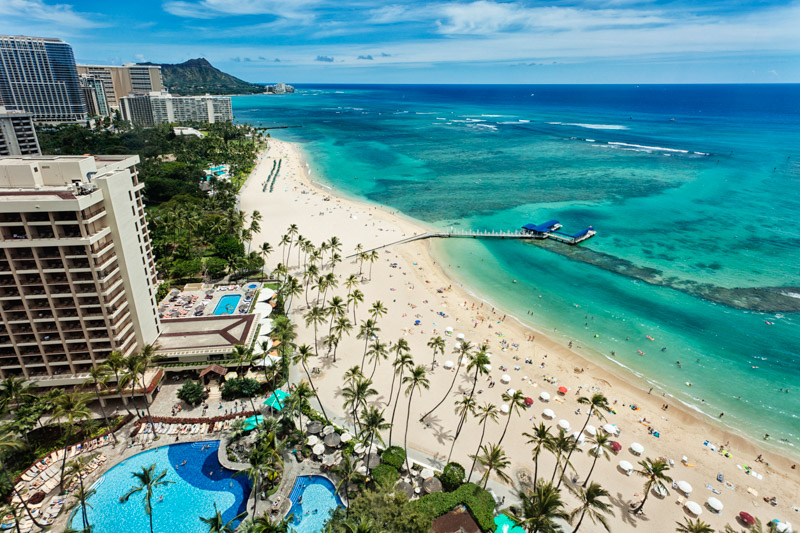 Aereal photo of Waikiki beach with view of Diamond Head mountain in the distance.