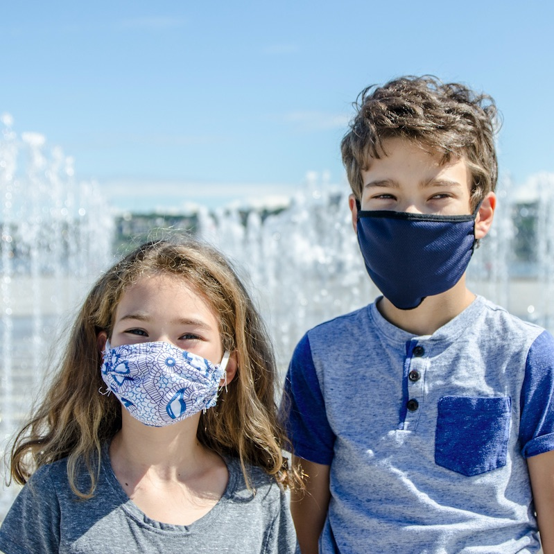 Boy and girl wearing face protection mask in city and smiling in Quebec City on a summer day
