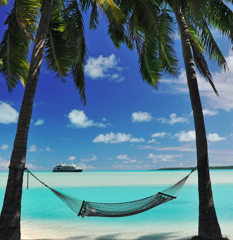 a hammock tied to two palm trees at the beach. cruise ship in the background