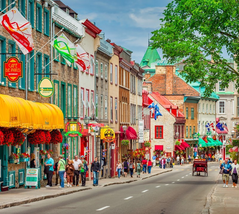 People walk past colorful store fronts and restaurants on Rue Saint-Louis in old town Quebec City, Canada on a sunny day.