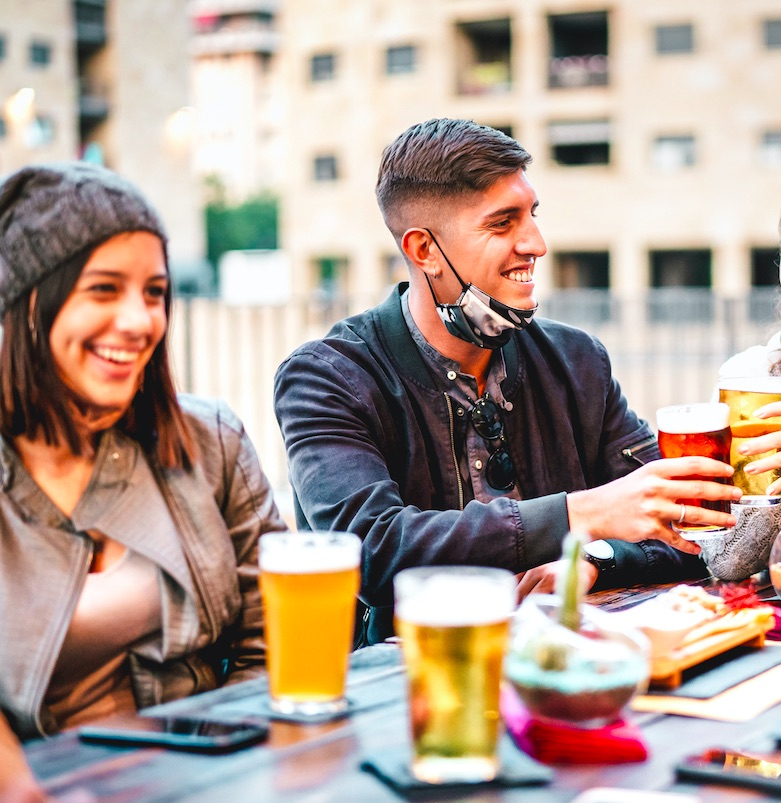 Young friends drinking beer with open face mask - New normal lifestyle concept