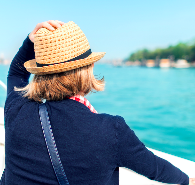 woman from the back holding her hat on her head on a cruise ship starring out at the water