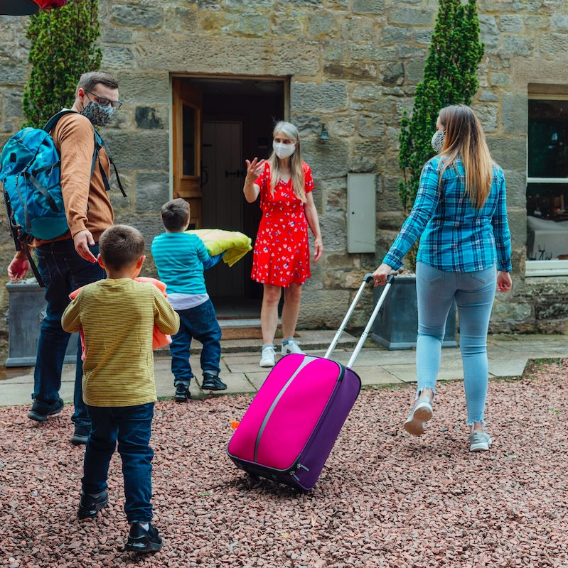 A shot of a young man and woman and their two young boys being greeted at a bed and breakfast by their host. They are all wearing casual clothing, carrying luggage are outside a country home.