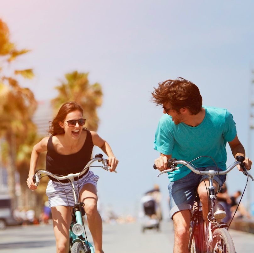 close up of two people riding their bikes in Spain on a sunny day and smiling